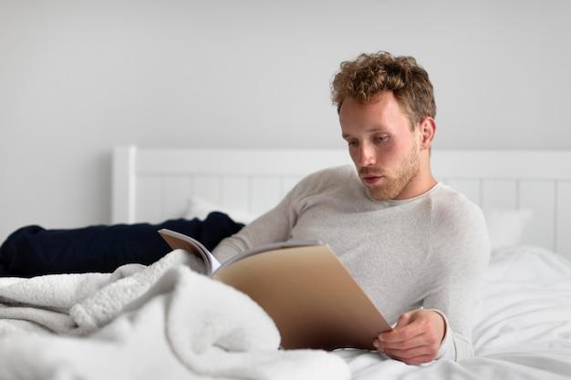 Uomo a tutto campo che legge un libro a letto