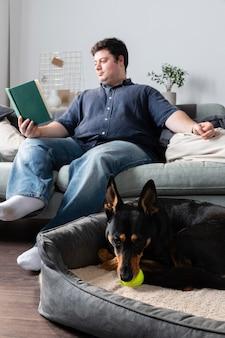 Uomo del colpo pieno che legge con il cane sveglio al chiuso