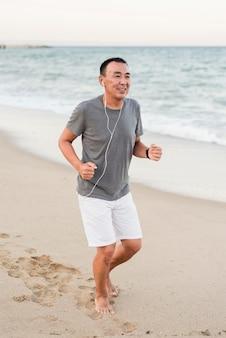 Uomo pieno del colpo che corre sulla spiaggia