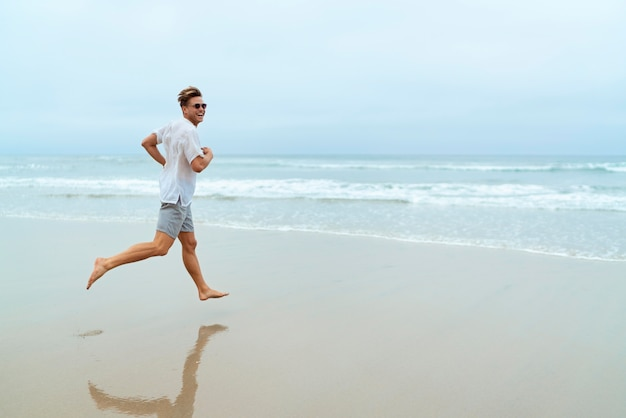 Uomo a tutto campo che corre sulla spiaggia