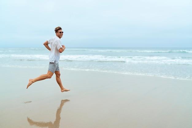 해변에서 달리는 풀샷 남자