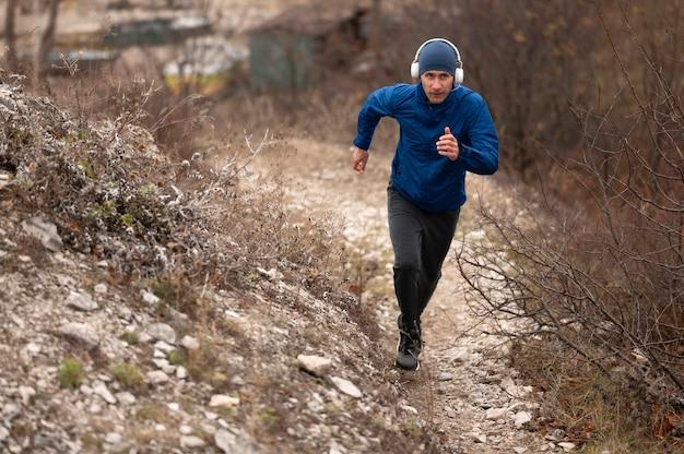 自然の中でトレイルを走るフルショットの男