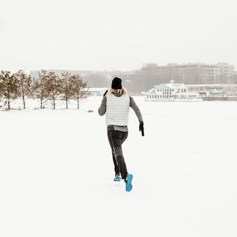 Uomo pieno del colpo che corre nella neve