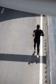 Full shot man running on street
