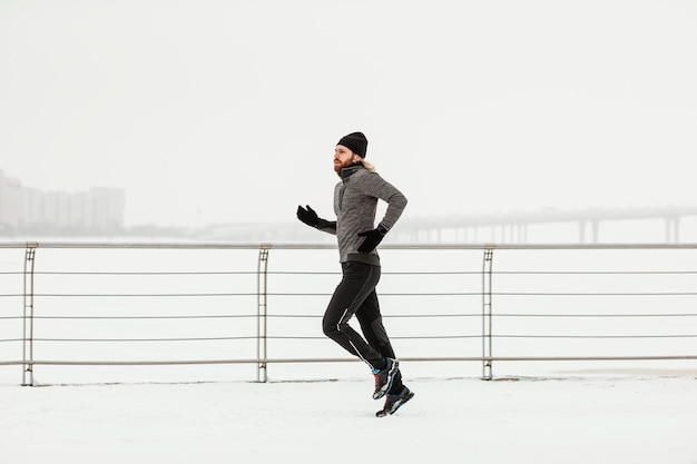 Full shot man running with snow