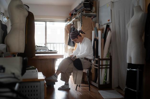 ワークショップで縫うフルショットの男