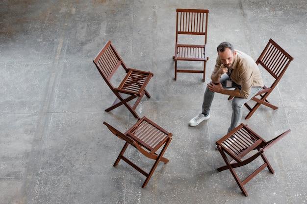 Uomo pieno del colpo che si siede sulla sedia