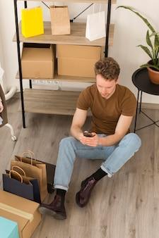 Uomo della foto a figura intera che si siede sul pavimento