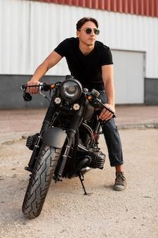 Uomo del colpo pieno che si siede sulla sua moto