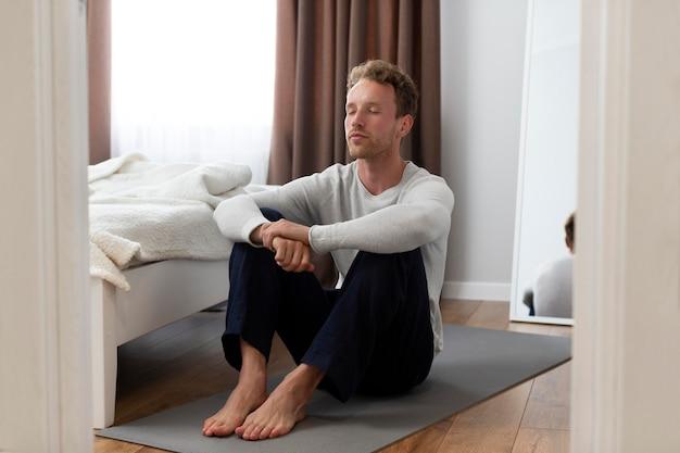 Uomo a tutto campo seduto sul tappetino