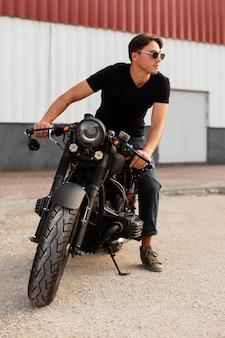 Uomo del colpo pieno che si siede sulla moto