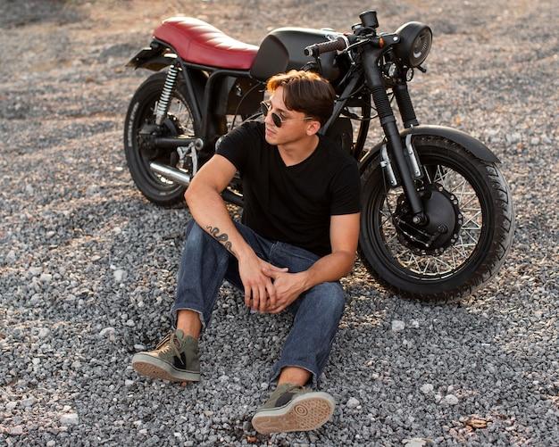 バイクの近くに座っているフルショットの男