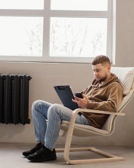 椅子に座っているフルショットの男