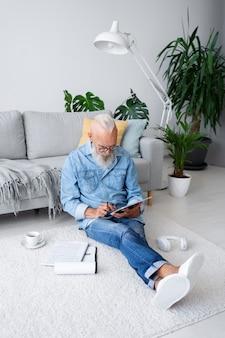Полный снимок человека, сидящего на полу с планшетом