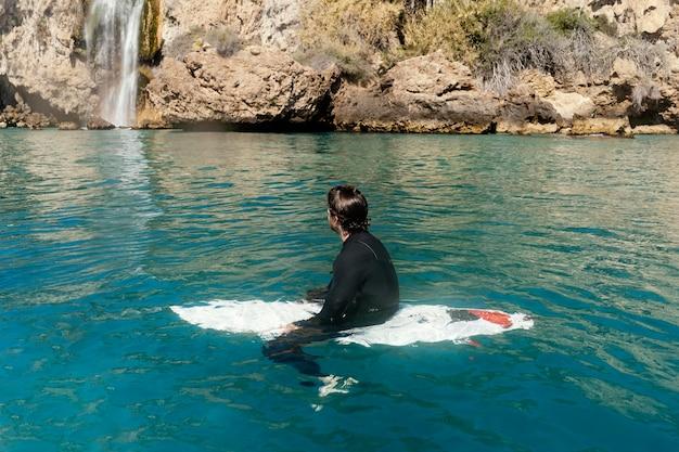 Полный выстрел человек, сидящий на доске для серфинга