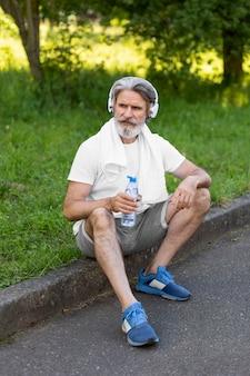 屋外に座っているフルショットの男