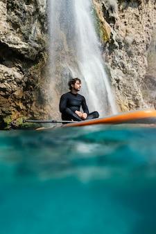Full shot man sitting on surfboard