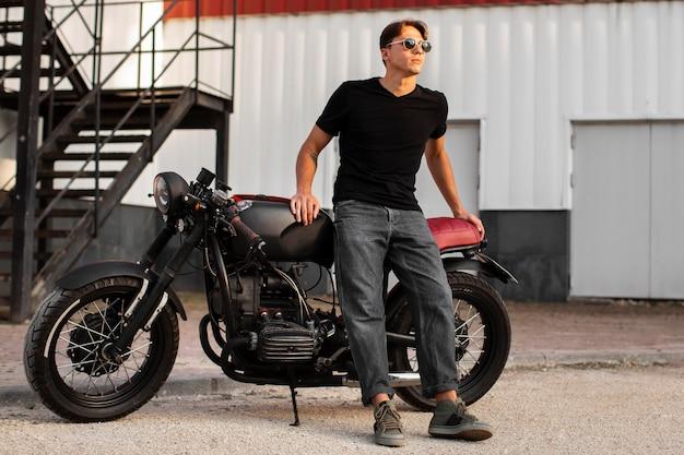 Full shot man standing near motorcycle