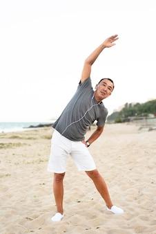 Uomo del colpo completo che si estende sulla spiaggia