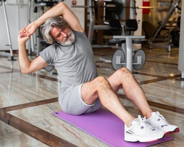 Full shot man stretching at gym