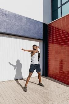 Full shot man stretching outdoors