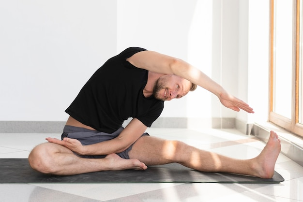 Full shot man stretching on yoga mat indoor