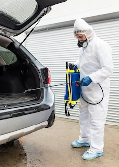 Uomo completo del colpo in vestito che disinfetta l'auto