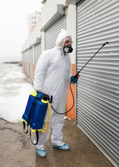 Uomo completo del colpo in vestito con disinfettante