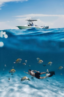 Full shot man swimming with fish