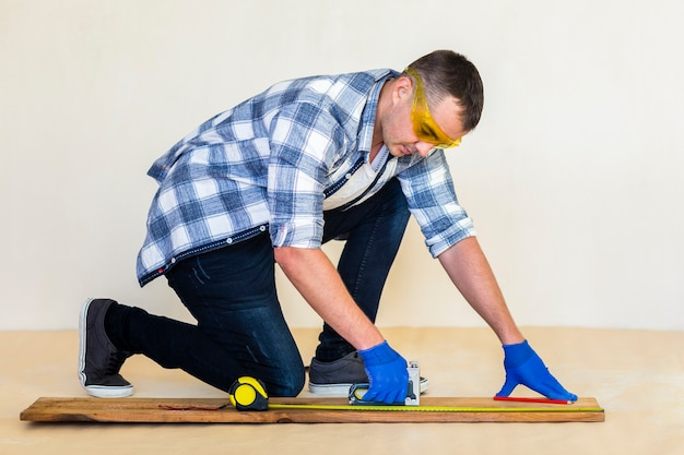 Full shot of man taking measure on wood