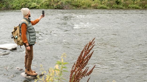 川の写真を撮るフルショットの男