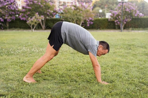 Uomo pieno del colpo che si allena sull'erba