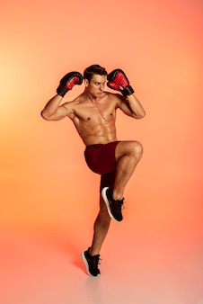 Full shot man training with boxing gloves