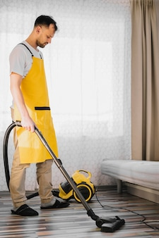 Full shot man vacuuming