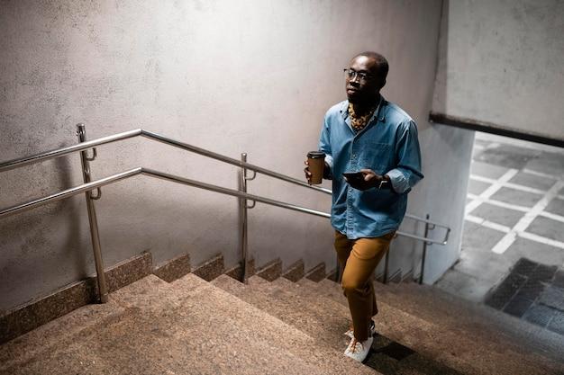 階段を上って歩くフルショットの男