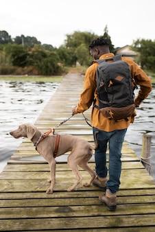 犬と一緒に歩くフルショットの男