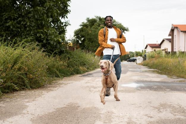 Full shot man walking with dog