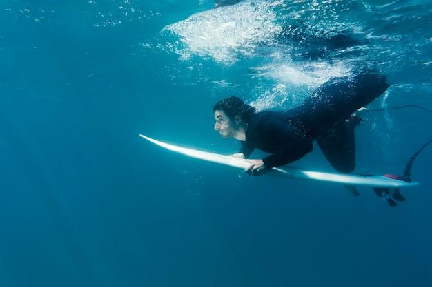 Uomo pieno del colpo sotto l'acqua