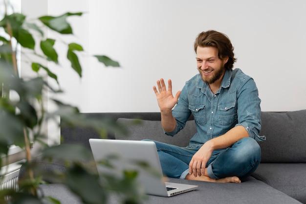 ノートパソコンで手を振っているフルショットの男