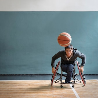 Uomo pieno del colpo in sedia a rotelle che gioca gioco