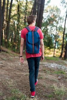 Полный выстрел человек с рюкзаком в лесу