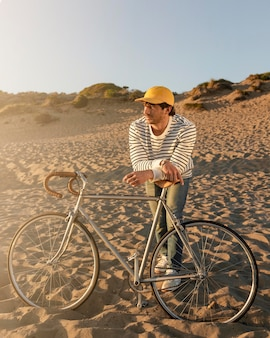 해변에서 자전거와 함께 전체 샷된 남자