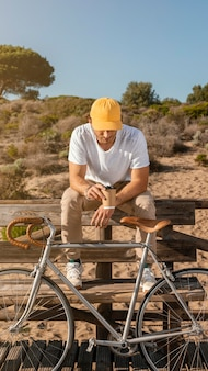 벤치에 자전거와 함께 전체 샷된 남자