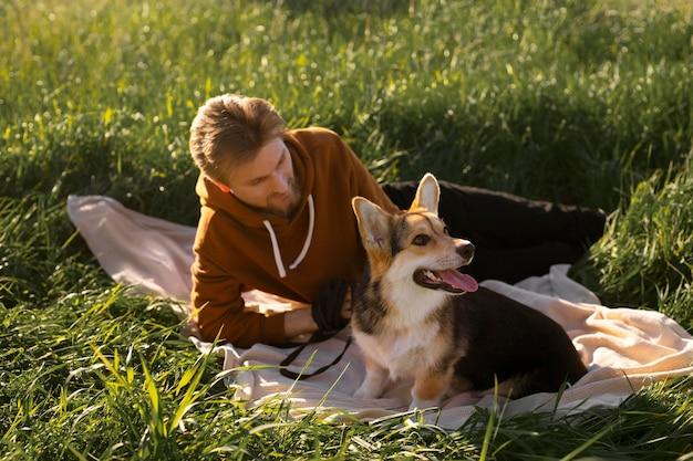 Uomo a tutto campo con cane sulla coperta