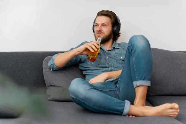 Uomo pieno del colpo con bevanda e cuffie