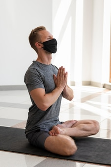 Полный снимок человека с маской для лица, делающего сукхасану на коврике внутри