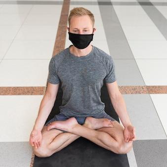Полный снимок человека с маской для лица, делающего позу сукхасана в помещении