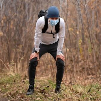Полный снимок человека с маской для лица в лесу