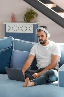 소파에 노트북으로 전체 샷된 남자