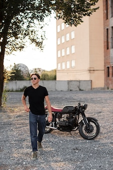 Full shot man with motorcycle outdoors